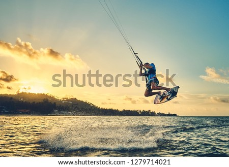 Young man kite boarder jumps over the sea at sunset            #1279714021