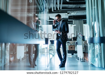 Successful lawyer dressed in formal wear standing in front of his office and using tablet for work. #1279782127