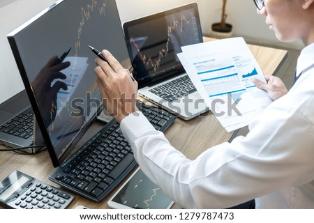 Stock exchange market concept, stock broker looking at graph working and analyzing with display screen, pointing on the data presented and deal on a exchange, Businessman trading stocks online. #1279787473