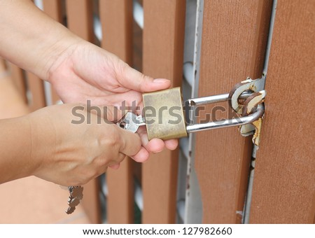 Closeup image of hand use key to open padlock and the brown wooden door #127982660
