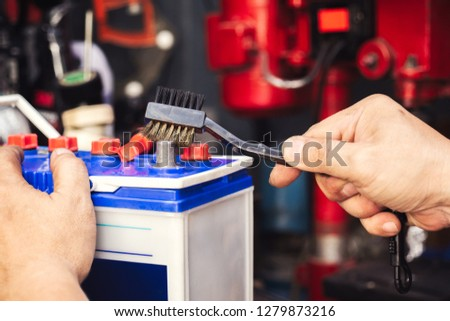 mechanic cleaning a battery connections ,brush and insert the brush into the car's battery terminals,especially if terminals are corroded, will help ensure  the battery lasts longer and performs well #1279873216