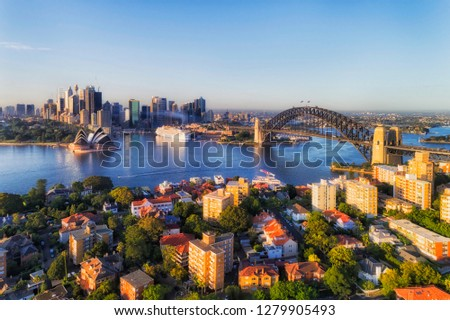 Blue Sydney Harbour surrounded by shores of Sydney city CBD and Lower NOrth Shore suburb Kirribilli connected by the Sydney Harbour bridge in elevated aerial view. Royalty-Free Stock Photo #1279905493