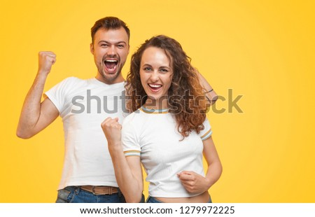 Cheerful modern man and woman in white t-shirts holding fists up being successful  #1279972225