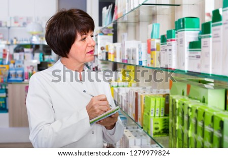 Portrait of diligent smiling  female druggist in white coat working in pharmacy #1279979824