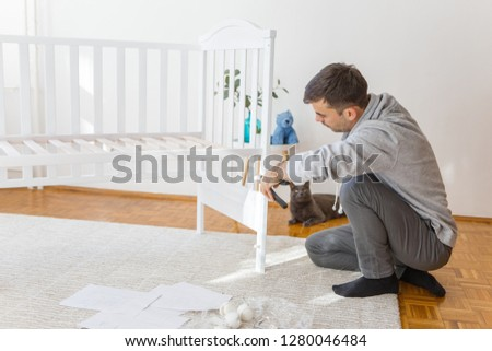 Father assembly crib for the newborn child, his cat is curious and looking whats going on #1280046484