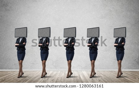 Business women in suits with TV instead of their heads keeping arms crossed while standing in a row in empty room with gray wall on background. #1280063161