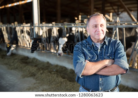 Adult farmer is standing at her workplace near cows at the farm. #1280063623