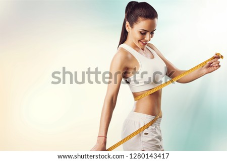 Weight loss, slim body, healthy lifestyle concept. Fit fitness girl measuring her waistline with measure tape on blue Royalty-Free Stock Photo #1280143417
