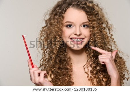 Healthy, beautiful smile, cute teen  with dental braces smiling . Portrait of a girl with orthodontic appliance. Girl brushing her teeth with toothpaste. #1280188135