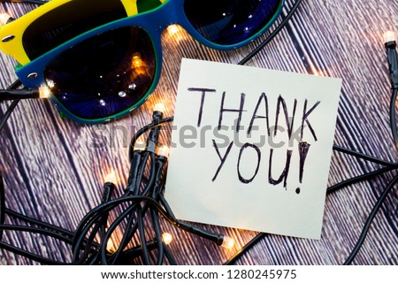 Scattered Lighted Tiny LED Stringlight on Wooden Surface. Two Colorful Sunglasses with Light Reflecting. Handwritten Message Expressing Gratitude Thankful. #1280245975