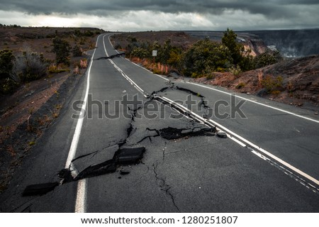 Damaged asphalt road (Crater Rim Drive) in the Hawaii Volcanoes National Park after earthquake and eruption of Kilauea (fume at upper right) volcano in May 2018. Big Island, Hawaii #1280251807