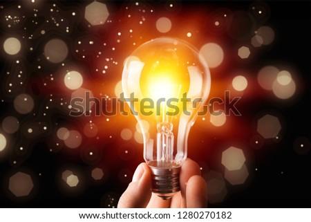 tungsten light bulb lit on garden background #1280270182