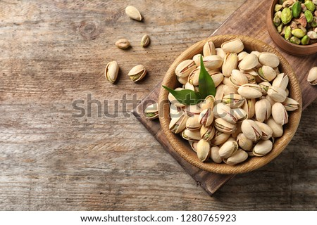 Organic pistachio nuts in bowl on wooden table, flat lay. Space for text #1280765923