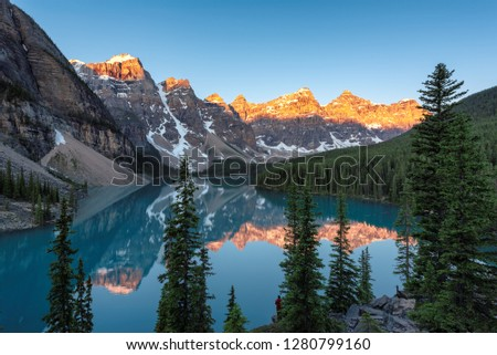 Beautiful sunrise under turquoise waters of the Moraine lake with snow-covered peaks above it in Canadian Rockies,  Banff National Park, Canada #1280799160