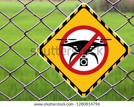 No drone zone Warning sign at fence wall, Prohibition sign to fly with drones on the net fence. No drone zone, No drone flying at perimeter fence netting of airport airspace or Detention Center #1280814796
