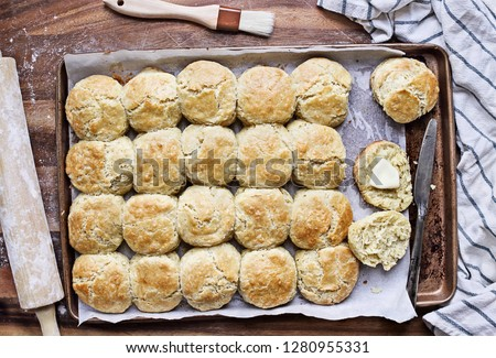 Freshly baked buttermilk southern biscuits or scones from scratch with rolling pin and basting brush on a baking sheet. Top view. #1280955331