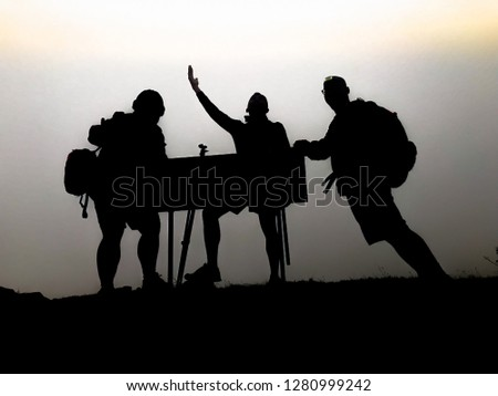 silhouette of tourist hiker acting on top of mountain #1280999242