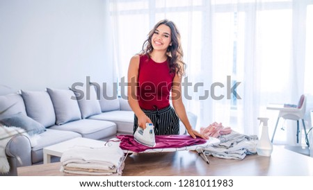 Happy woman housewife ironing clothes iron in laundry at home. Young Smiling Woman Ironing Clothes On  Board At Home. Closeup of woman ironing clothes on ironing board  #1281011983