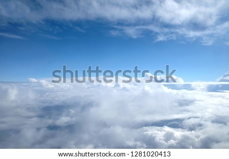Beautiful sky landscape with view from the plane above dense white clouds high in the stratosphere on a sunny day horizontal photo