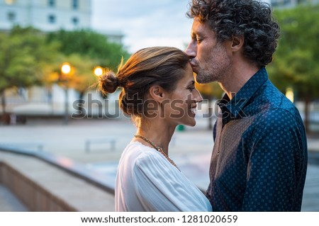 Mature husband kissing wife on forehead in the street in the evening. Romantic senior man giving a kiss to her woman in the city street. Loving middle aged couple in love at dusk. #1281020659