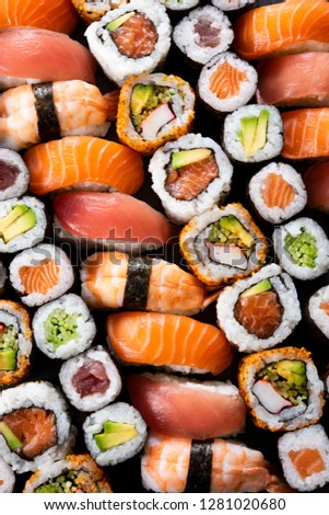 Top view of variety of sushi food. High angle view of nigiri, maki, hosomaki, uramaki and roll with tuna, salmon, avocado and shrimp in a row. Traditional japanese food with raw fish and rice. #1281020680