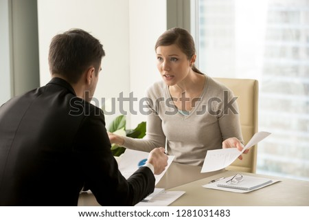Angry businesswoman arguing with businessman about paperwork failure at workplace, executives having conflict over responsibility for bad work results, partners disputing about contract during meeting #1281031483