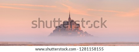 Le Mont Saint Michel in Normandy, France on a foggy morning at sunrise. #1281158155