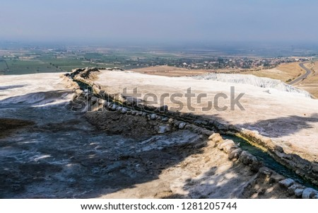 Cascades of terraced baths among the mountain peaks of Pamukkale in Turkey. Pamukkale contains hot springs and travertines, terraces of carbonate minerals left by running water. #1281205744