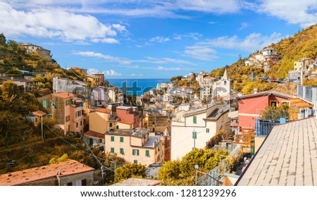 Autumn view of Riomaggiore town and Ligurian Sea at noon time. Riomaggiore is one of the five towns of Cinque Terra located on the coast of Ligurian Sea in Italy. #1281239296