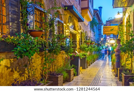 ANTALYA, TURKEY - MAY 9, 2017: The narrow streets of Kaleici, decorated with plants and flowers in pots, look very attractive and cozy for tourists, enjoying their evening walks, on May 9 in Antalya. #1281244564