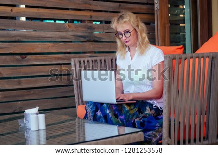attractive woman of 40years with a mobile phone and laptop at the beach cafe on the background of the sea.remote work freelancer business blonde woman Royalty-Free Stock Photo #1281253558