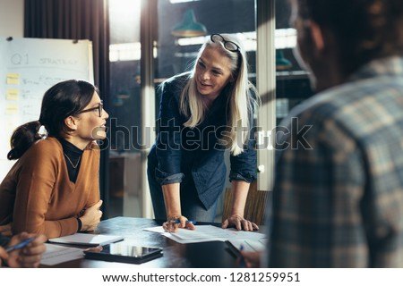 Senior business woman explaining business matters to her team in a boardroom. Mature manager planning new strategy with colleagues in meeting. #1281259951