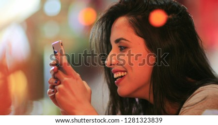 Candid surprise reaction of girl in front of cellphone reading text message smiling and laughing at night at coffee shop #1281323839