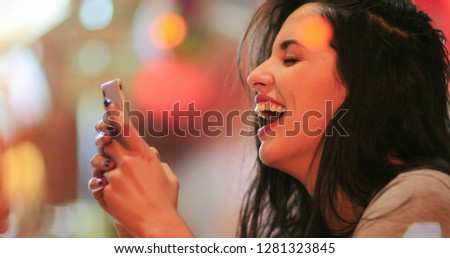 Candid surprise reaction of girl in front of cellphone reading text message smiling and laughing at night at coffee shop #1281323845