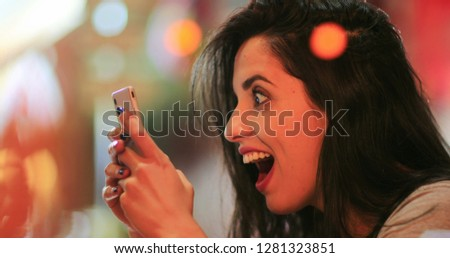 Candid surprise reaction of girl in front of cellphone reading text message smiling and laughing at night at coffee shop #1281323851