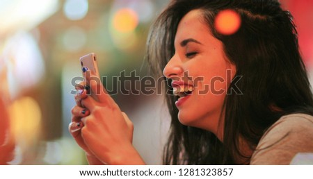Candid surprise reaction of girl in front of cellphone reading text message smiling and laughing at night at coffee shop #1281323857