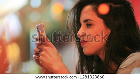 Candid surprise reaction of girl in front of cellphone reading text message smiling and laughing at night at coffee shop #1281323860