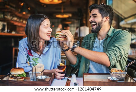 Happy young couple having breakfast in a cafe. Love, dating, food, lifestyle concept #1281404749