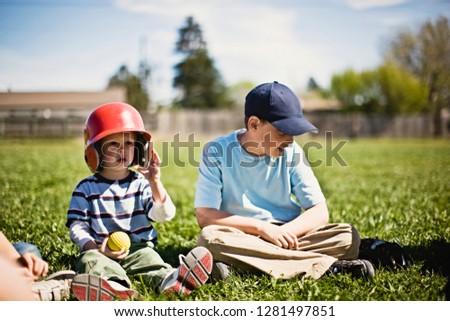 Brothers sitting on baseball field