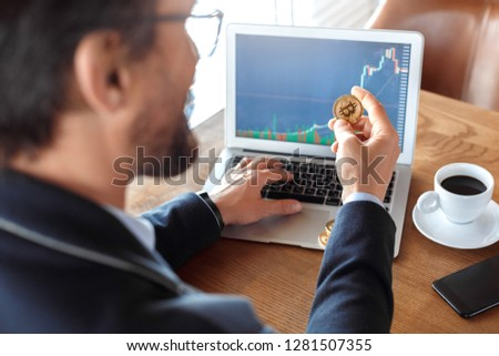 Mature man trader sitting at table at cafe with cup of coffee browsing laptop checking online trading chart holding cryptocurrency coin back view close-up #1281507355