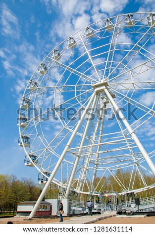 Ferris wheel an amusement-park or fairground ride consisting of a giant vertical revolving wheel with passenger cars suspended on its outer edge. #1281631114
