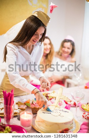 The beautiful young bride stewardess standing near the festive table at the hen party and cutting a cake #1281631348