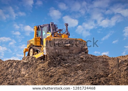 Yellow dozer pushes a pile of sand. Bulldozer working working on sand dune. #1281724468