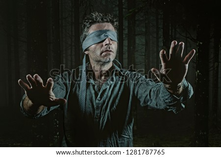 young confused and scared man blindfolded with necktie playing internet trend dangerous viral challenge with eyes blind lost in dark forest background guided by intuition #1281787765