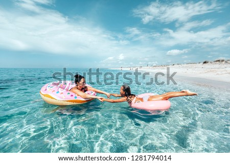 Mom with child chilling on lilo in the sea water. Family relaxing on inflatable rings on the beach. Summer vacations, idyllic scene. #1281794014