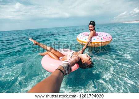 Mom with child chilling on lilo in the sea water. Family relaxing on inflatable rings on the beach. Summer vacations, idyllic scene. #1281794020