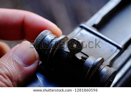 Close up Rear sight of the gun,The left hand is adjusting the center, aiming at number 2. #1281860596