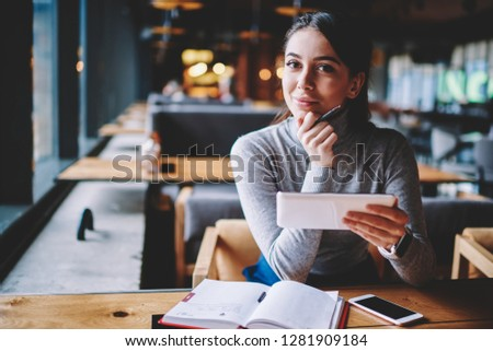 Portrait of beautiful young smiling blogger looking in camera while enjoying break at cafe and creating new publication for own website, happy hipster girl holding electronic device and chatting #1281909184