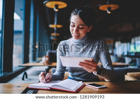 Smiling successful young woman received message on gadget checking notification indoors, positive cheerful hipster girl reading news via modern device at cafeteria and writing article for share #1281909193