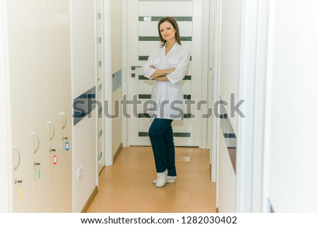 young attractive attractive female doctor in a white dressing gown stands in a bright room #1282030402